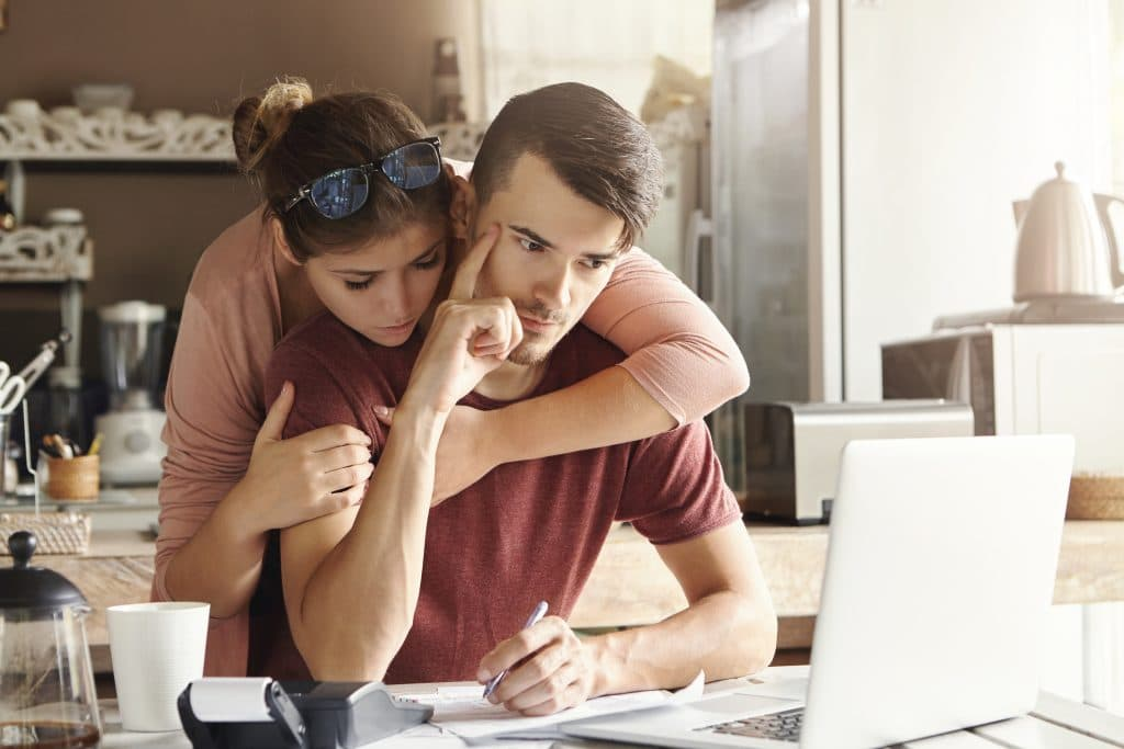 Young couple faces financial troubles. At kitchen table on laptop sulking over bills. Concerned look on face. Wife with arm around husband consoling him from behind.