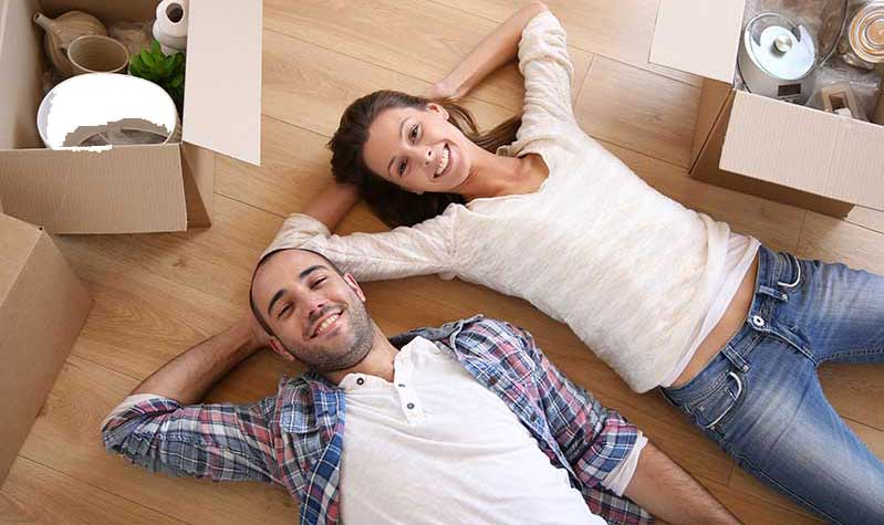 Young satisfied couple lying on their backs, smiling at camera, with arms behind their heads in new home, surrounded by moving boxes. and belongings.